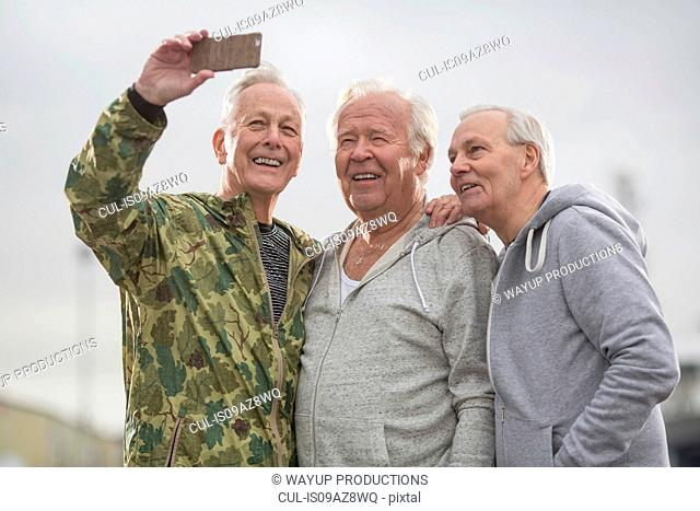 Senior friends wearing sports clothes using smartphone to take selfie