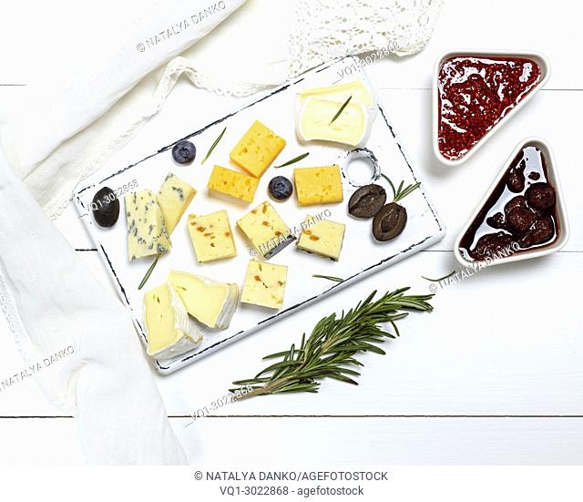 small pieces of brie cheese, roquefort, camembert, cheddar and cheese with walnuts on a white wooden board