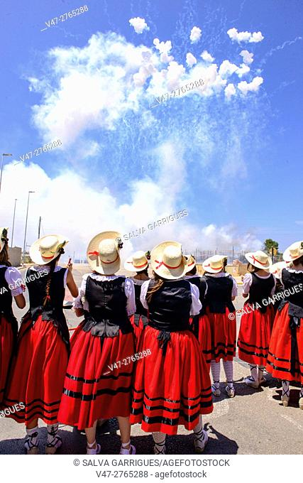 Girls watching the fireworks with the traditional costume of shepherdesses in the celebrations of Almussafes, Valencia, Spain, Europe