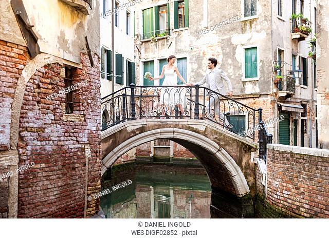 Italy, Venice, bridal couple running on little bridge