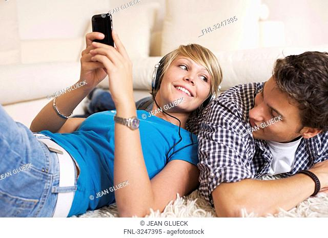 Teenager couple lying on carpet and listening to music, low-angle view