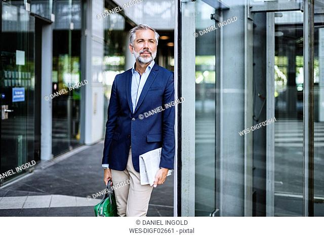 Businessman standing at building with bag and newspaper