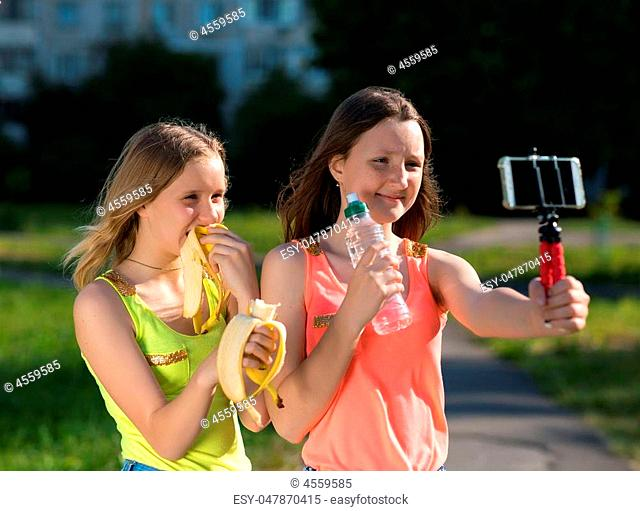 Young girls schoolgirl. Summer in nature. In the hands holding a bottle of water .. Baby bloggers and vlogers A new video for subscribers