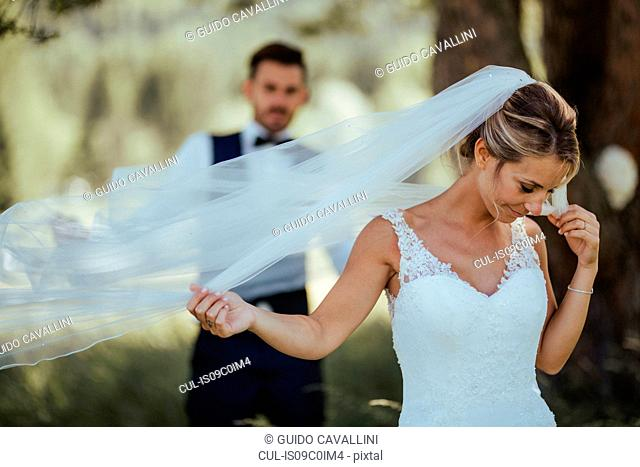 Bride and groom holding delicate wedding veil in woodland