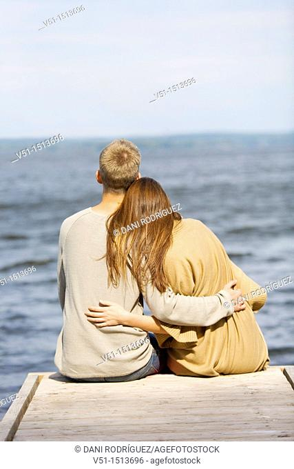 Young couple relaxing, sitting in a Pier in Wansee, Berlin