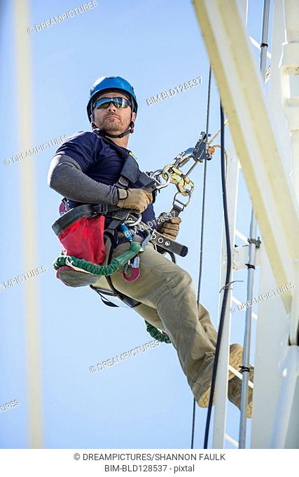 Caucasian worker harnessed to cell tower