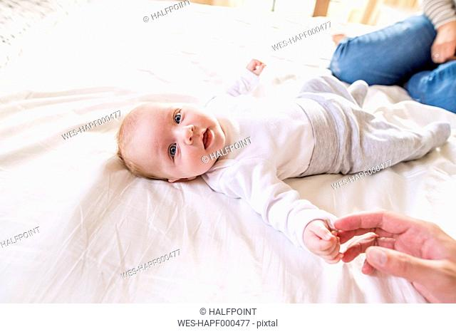 Baby lying on bed with parents