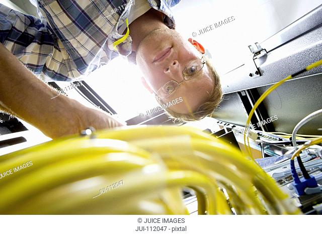 Technician checking wiring of server in data centre
