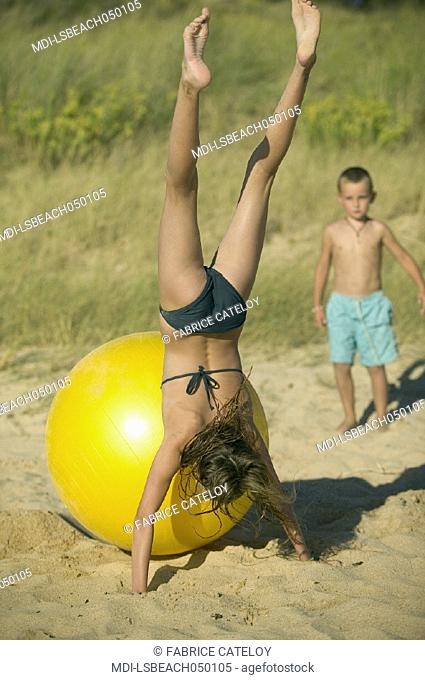 Young girl playing with a big yellow balloon on the sand beach - Little boy looking at her in the background