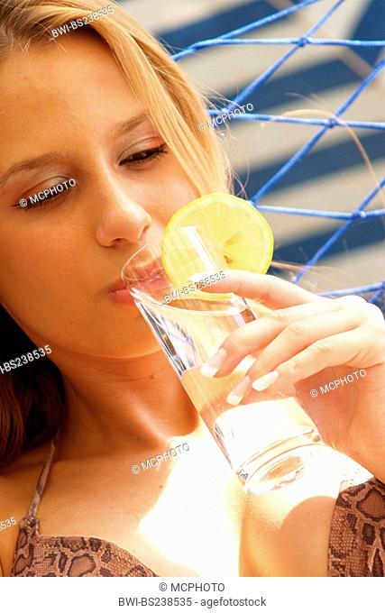 young woman in a hammock drinking water from a Glas decorated with a lemon slice