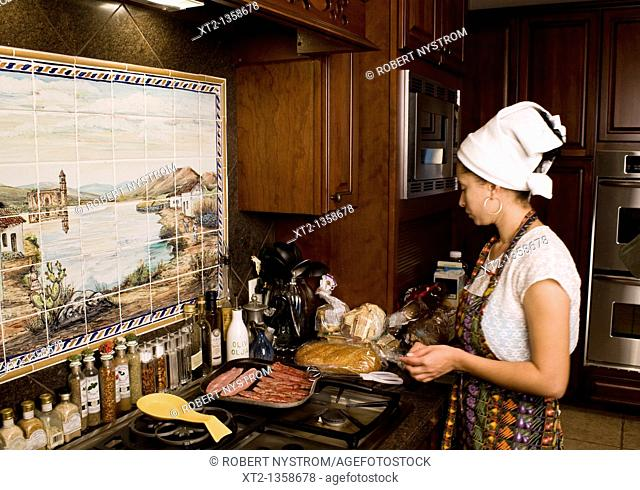 Woman in a kitchen cooking breakfast wearing an apron and hair towel