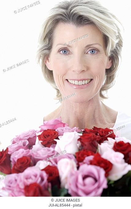 Senior woman smiling and holding bouquet of flowers