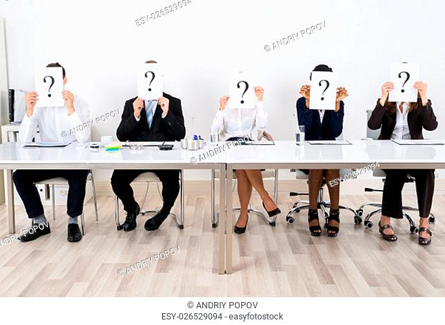 Businesspeople Holding Question Mark Sign In Front Of Their Face