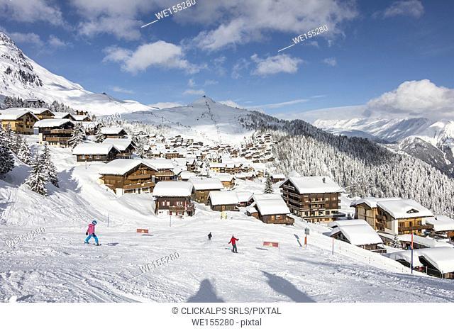 Skiers on the ski slopes frame the typical alpine village Bettmeralp district of Raron canton of Valais Switzerland Europe