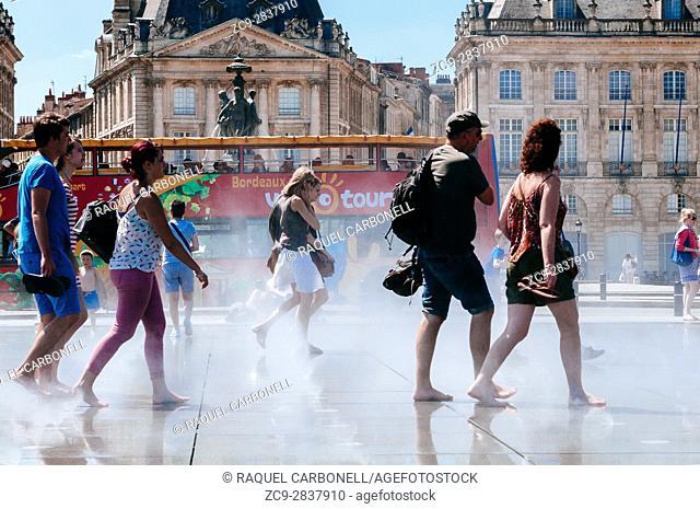 Tourists paddling in water mirror fountain Place de la Bourse, Bordeaux, France