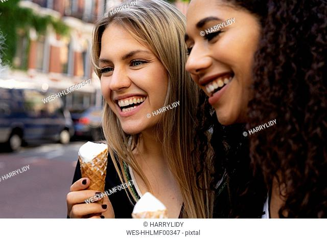 Two laughing girlfriends having fun, eating ice cream