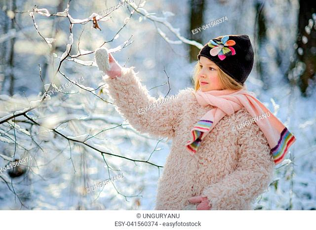 Portrait of the girl of 8-9 years in the winter park. The girl touches a snow-covered branch. From a frost of a cheek of the little belle became ruddy
