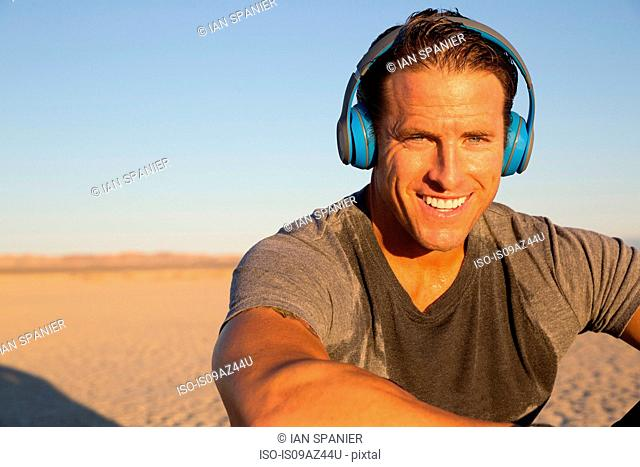 Man training, listening to headphones on dry lake bed, El Mirage, California, USA