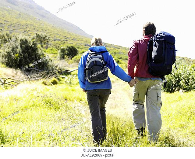 Couple holding hands hiking