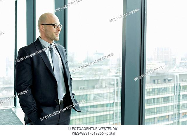 Confident businessman on office floor looking out of window