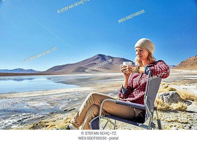 Bolivia, Laguna Colorada, woman sitting on camping chair at lakeshore drinking from cup