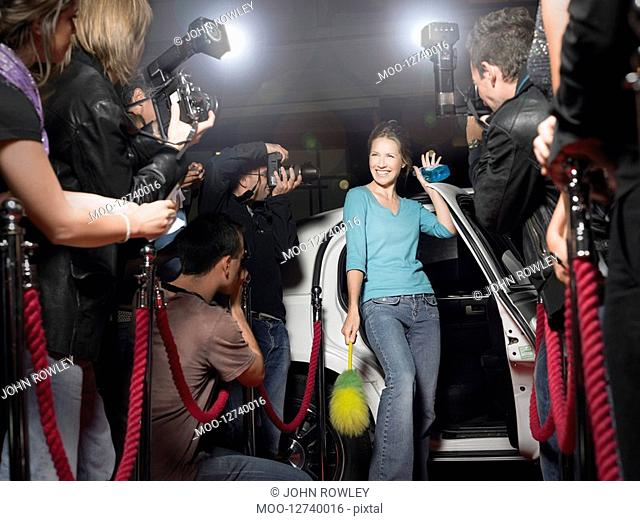 Woman with cleaning equipment getting out of limousine in front of paparazzi