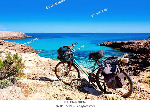 Menorca Cala des Talaier beach with aged grunge bicycle