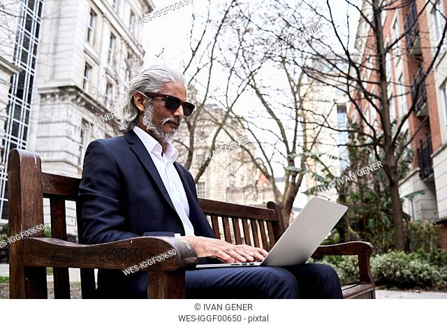 UK, London, senior businessman sitting on bench outdoors working on laptop