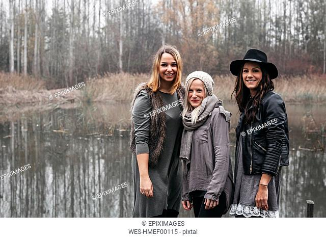 Group picture of three happy friends in autumnal nature