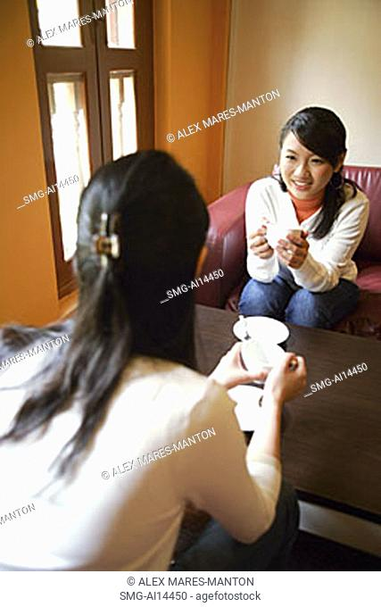 Two young women, holding cups of coffee, talking, over the shoulder view