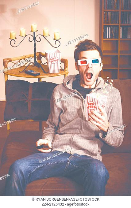Crazy pastel image of a shocked man wearing 3d movie glasses while watching a horror movie with popcorn. Home theatre concept