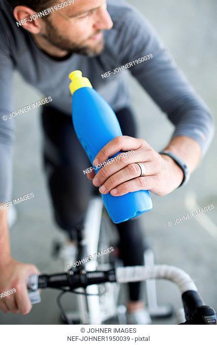 Mid adult man indoor cycling, studio shot