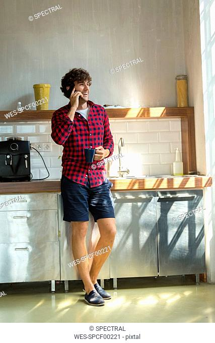 Young entrepreneur standing in company kitchen, drinking coffee, using smartphone