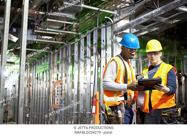 Workers using tablet computer on site
