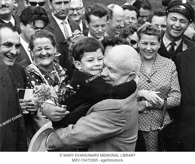 Nikita Khrushchev (1894-1971), Russian Soviet leader, seen here hugging a little boy who has just presented him with a bunch of flowers, surrounded by happy