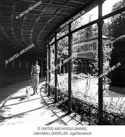 Eine junge Frau geht mit ihrem Hund durch eine Galerie spazieren, Deutschland 1930er Jahre. A young woman walking the dog through a cloister at Stuttgart