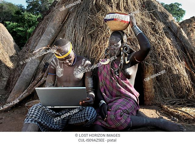 Man of the Mursi Tribe with laptop, sitting beside his wife, Omo Valley, Ethiopia