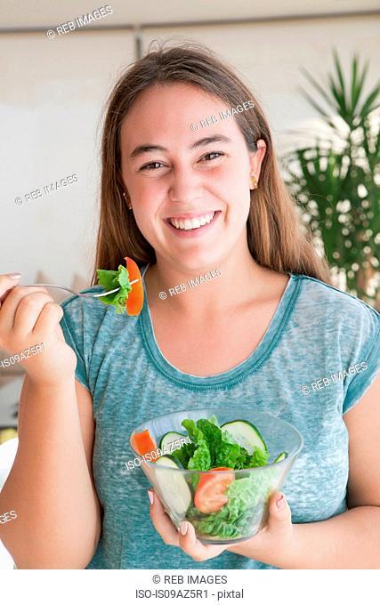 Teenage girl holding bowl of salad looking at camera smiling
