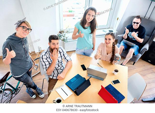 High-angle view of a group of young cheerful people showing thumbs up as a sign of happiness, for co-working in a modern shared office space