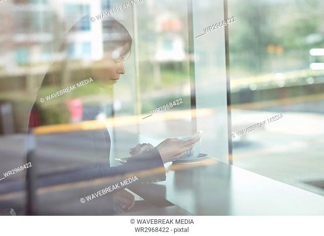 Businesswoman using mobile phone in cafeteria