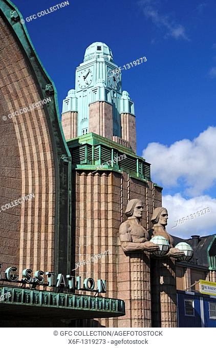 Clock tower and two pairs of statues made of granite holding the spherical lamps at the entrance to the Central railway station, Helsinki, Finland