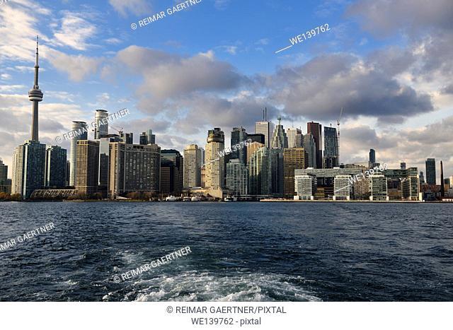 Wake of Wards Island ferry with Toronto city skyline highrise towers