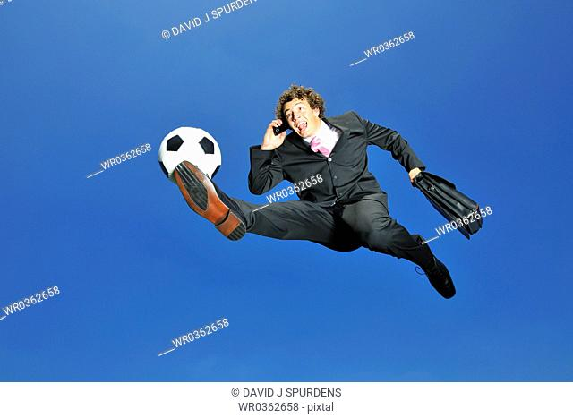 Businessman on cell phone volleys ball