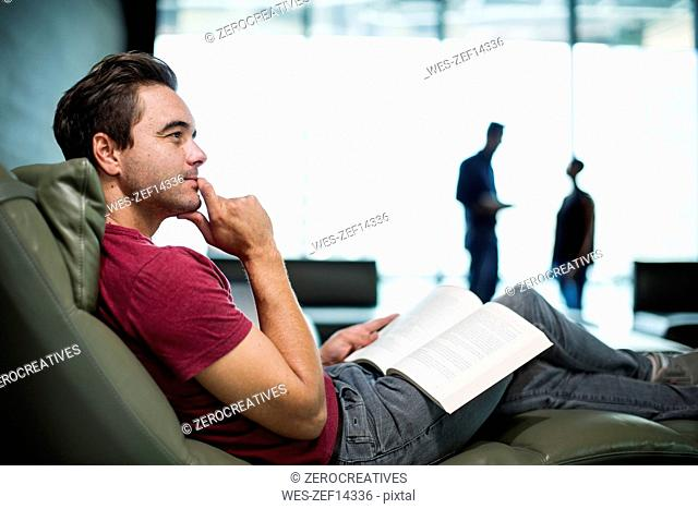 Man in office sitting in armchair, reading a book