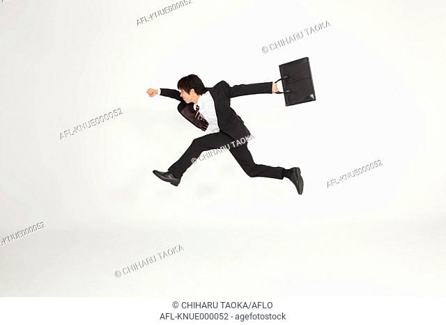 Japanese businessman running in mid-air