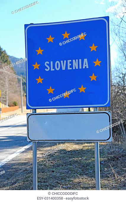 blue road sign with yellow stars in the border area between slovenia and other country