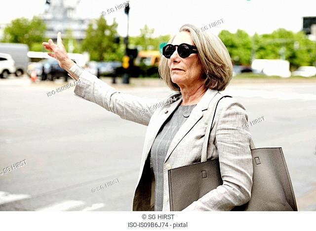 Senior businesswoman hailing taxi