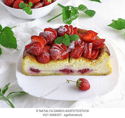 Cheesecake of cottage cheese and fresh strawberries on a white ceramic plate, top view