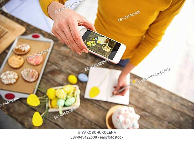 Top view of woman in kitchen making photo of her hand writing in notebook. Basket with pained eggs, cookies and glazed easter cake are standing on table
