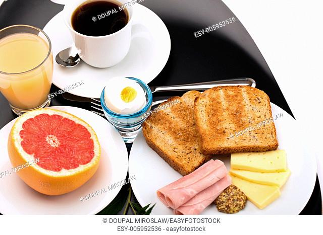 Breakfast with toast, ham, cheese, egg, grapefruit, juice and cup of coffee